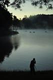 Fotograf, der Schuss auf Seeufer nimmt lizenzfreie stockbilder