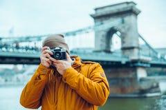 Fotograf des jungen Mannes, der alte Brücke auf Hintergrund schießt Lizenzfreie Stockbilder