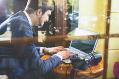 Fotograf des jungen Mannes, der am Café, unter Verwendung des Laptops arbeitet Lizenzfreie Stockfotos