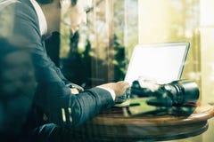 Fotograf des jungen Mannes, der am Café, unter Verwendung des Laptops arbeitet Lizenzfreies Stockbild