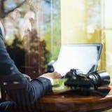 Fotograf des jungen Mannes, der am Café, unter Verwendung des Laptops arbeitet Lizenzfreies Stockfoto