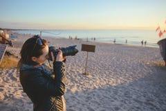 fotograf för yrkesmässig kvinna på stranden Arkivbild