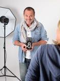 Fotograf i studion som tar skott av kvinnamodellen Arkivfoton