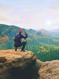 Fotograf im Freien mit Stativ und Kamera auf dem Felsendenken Herbstliches Tal Lizenzfreie Stockfotografie