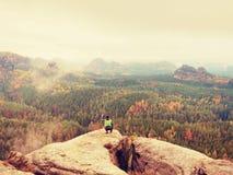 Fotograf macht Foto der Frühlingsnatur von den scharfen Felsen Wanderer im Aufenthalt der grünen Jacke mit Kamera auf Stativ Lizenzfreie Stockfotos