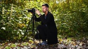Fotograf macht Fotos mit einem Stativ im Sommerwald stock footage