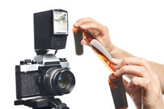 Fotograf med den negativa filmen för färg nära den isolerade SLR kameran Royaltyfri Bild