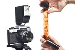 Fotograf med den negativa filmen för färg nära den isolerade SLR kameran Arkivfoto