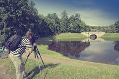 Fotograf med kameran i sommarträdgården på banken av sjön, en retro effekt Royaltyfria Foton