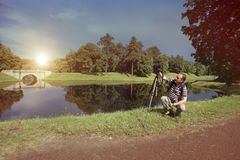 Fotograf med kameran i sommarträdgården på banken av sjön, en retro effekt Arkivbild
