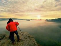 Fotograf mit Auge am Sucher der Kamera auf Stativaufenthalt auf Klippe und macht Fotos, Gesprächsfreunde Stockfotografie
