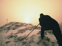 Fotograf mit Auge am Sucher der Kamera auf Stativaufenthalt auf schneebedeckter Klippe und macht Fotos Lizenzfreie Stockbilder