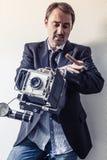 Fotograf mit der alten Kamera, die seine Uhr betrachtet Stockfoto