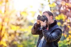 Fotograf mit der Berufsdigitalkamera, die Fotos macht Stockbilder