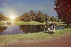 Fotograf mit der Kamera im Sommergarten auf der Bank des Sees, ein Retro- Effekt Stockfotografie