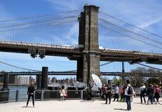Fotograf mit der Mannschaft, die junges Modell unter Brooklyn-Brücke schießt Stockfoto