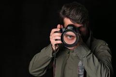 Fotograf och hans öga i linsen close upp Svart bakgrund arkivfoto