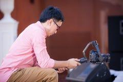 Fotograf- och videotillverkaremannen rymmer DSLR-kameran på hans hand till framställning av längd i fot räknat Arkivfoton