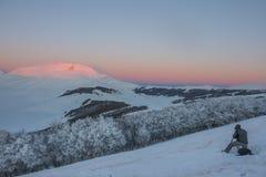 Fotograf pracuje w górach w zimie przy zmierzchem z s Zdjęcia Royalty Free
