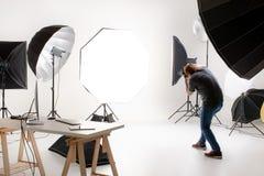 Fotograf pracuje w nowożytnym oświetleniowym studiu z wiele rodzajami obrazy stock