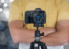 fotograf ręki składali z kamerą z tripod w przodzie Srebny bokeh behind Zdjęcia Stock