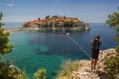 Fotograf robi fotografii Sveti Stefan wyspie w Budva, Mon zdjęcie royalty free