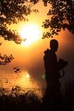 Fotograf am See vor der untergehenden Sonne Stockbild