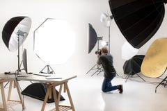 Fotograf som arbetar i modern belysningstudio med många sorter royaltyfria bilder