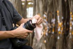 Fotograf som gör ren en kameralins med en micro Royaltyfri Foto