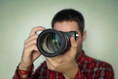 Fotograf som rymmer den mirrorless kameran för kontroll hans foto i selektiv fokus Royaltyfria Bilder