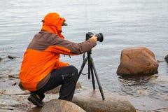 Fotograf som ser in i digital kamera fotografering för bildbyråer