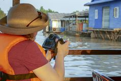 Fotograf som skjuter sväva fiskeläget av Tonle Sap River i Cambodja arkivfoton