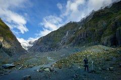 Fotograf som tar ett fotografi i franz josef glaciär en av mest populär naturlig resande destination i southland Nya Zeeland arkivbild