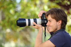 Fotograf som tar ett fotografi som är utomhus- med en dslrkamera Arkivfoto