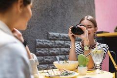 Fotograf som tycker om hennes ockupation, medan göra fotoet av vän arkivbilder