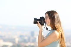 Fotograf som utomhus tar foto med en dslrkamera arkivbild