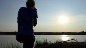 Fotograf strzela arty sunpath na jeziorze przy zmierzchem w mo zbiory wideo