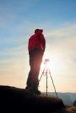 Fotografa pobyt z tripod na falezie i główkowaniu Marzycielski fogy krajobraz, pomarańczowy mglisty wschód słońca w pięknej dolin Obraz Stock