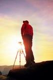 Fotografa pobyt z tripod na falezie i główkowaniu Marzycielski fogy krajobraz, pomarańczowy mglisty wschód słońca w pięknej dolin Fotografia Royalty Free