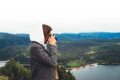 Fotografa podróżnika turystyczna pozycja na zieleń wierzchołku na halnym mieniu w ręki fotografii cyfrowej kamerze, wycieczkowicz obrazy stock