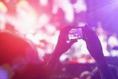 Fotografando con il telefono cellulare al concerto fotografia stock