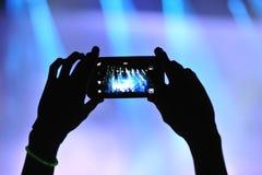 Fotografando con il telefono cellulare al concerto Immagini Stock