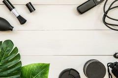 FotografArbeitsplatz mit Objektivkappe, schwarze Werkzeuge, Fernsteuerungs- und tropischer Blattebene der Linse, des Falles, der  Lizenzfreies Stockbild