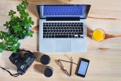 Fotografarbetsplats, kugghjul, bästa sikt av skrivbordet med bärbara datorn royaltyfri fotografi