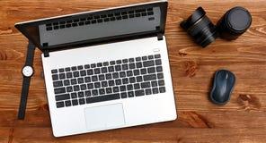 Fotografarbetsplats table trä Vit bärbar dator, datormus, armbandsur, två linser för kameran Arkivfoto