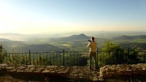 Fotografe com a câmera na ação dentro do amanhecer no ponto de vista Montes que colam para fora da paisagem lisa, filme