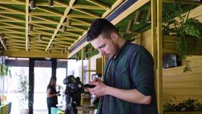 Fotografen använder telefonen för att meddela med kameran på en WiFi arkivfilmer