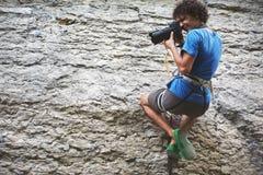 Fotografen hänger på ett rep på klippan, och forsar vaggar klättrare Royaltyfri Bild