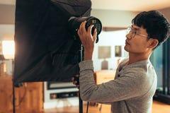 Fotografen justerar ljus styrka för softbox för fors arkivbild