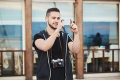 Fotografen lieben diesen Smartphone Porträt im Freien des hübschen europäischen Fotografen in der modischen Kleidung, die Foto an Lizenzfreie Stockfotos